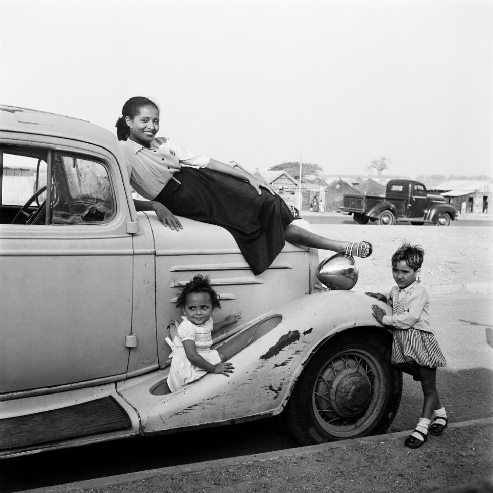 A woman, Madame Gomez, poses on top of a car with two young children standing by the vehicle
