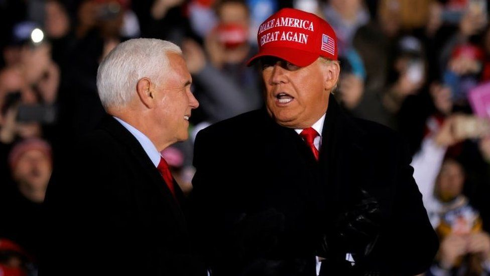 US President Donald Trump talks to Vice President Mike Pence, as he holds a campaign rally at Gerald R. Ford International Airport in Grand Rapids, Michigan, US on 2 November 2020
