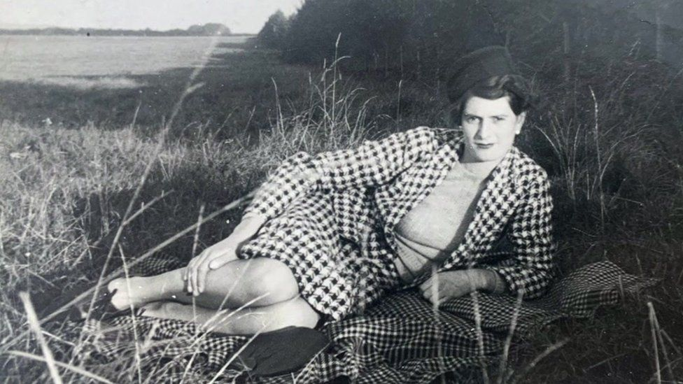 Kathleen as a young woman lying on the grass
