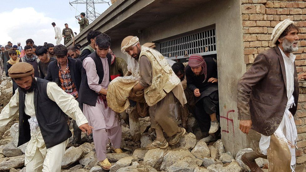 People carry out an injured person from the rubble
