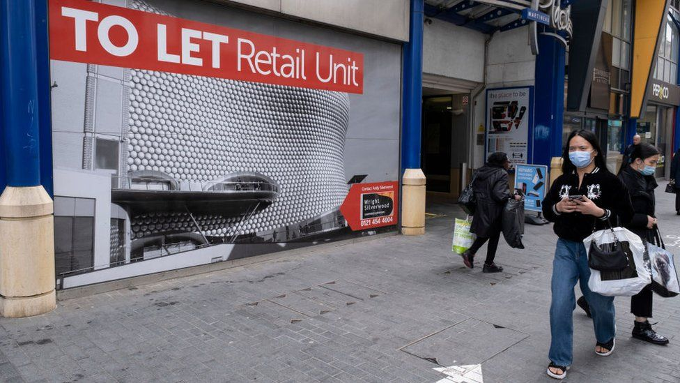 A woman walking past a closed down shop