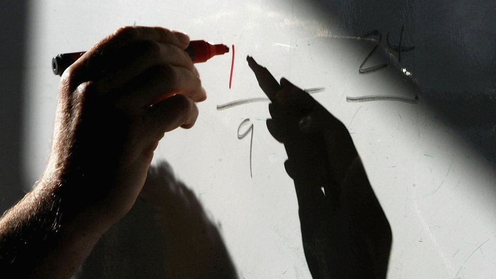 Teacher writing on white board during lesson
