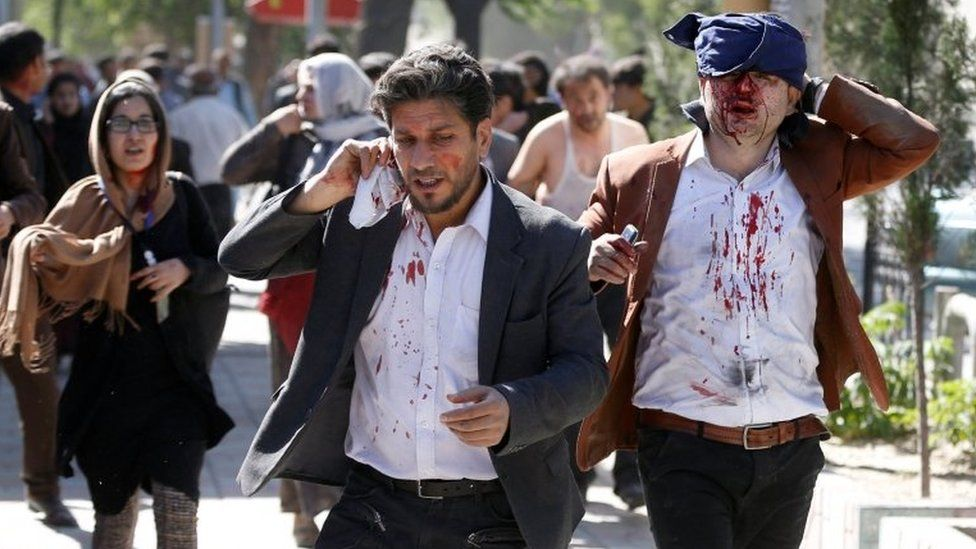 Injured Afghans run from the site of a blast in Kabul, Afghanistan May 31, 2017.