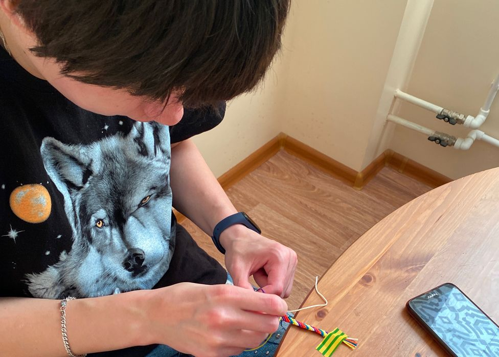 Nina weaving a friendship bracelet