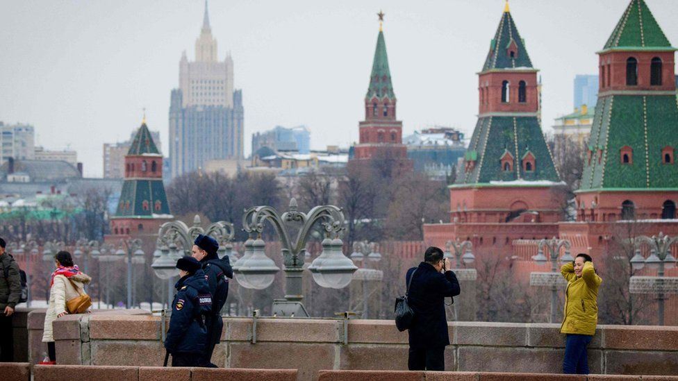 Police officials patrol among sightseers on a bridge outside The Kremlin in Moscow