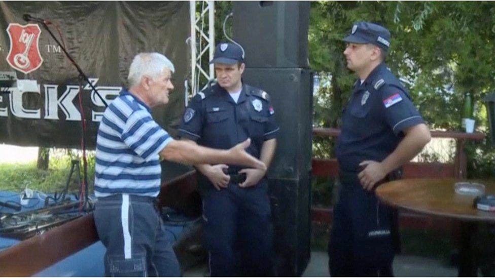 A man talks to police officers at a cafe after a shooting during a local festival in the village of Zitiste, north of Belgrade, Serbia in this still image from video taken 2 July 2016.