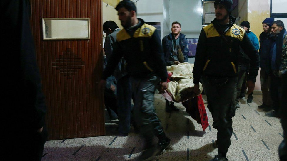 Syrian paramedics carry a victim into a make-shift hospital in the besieged rebel-held town of Douma, on January 3, 2018