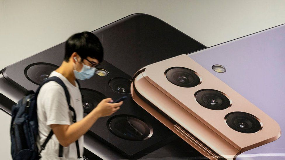A man uses a smartphone as he walks past the South Korean multinational electronics Samsung advertising the Samsung Galaxy s21 5G smartphone on a billboard in Hong Kong.