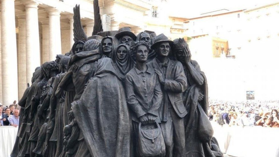 """Depictions of refugees towards the back of the """"Angels Unaware"""" sculpture"""