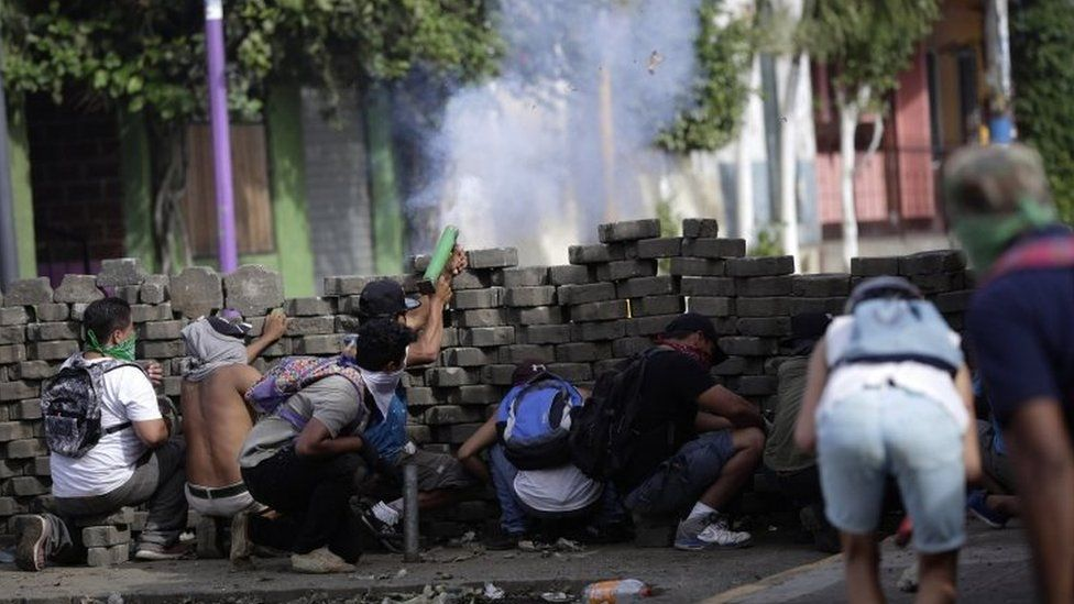 """Protesters take cover behind a makeshift barrier during ongoing protests in Masaya, Nicaragua, 09 June 2018. Nicaragua saw renewed protests after President Daniel Ortega failed to respond to a letter calling for """"democratization"""" of the country."""