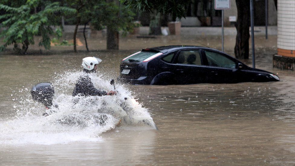 A man drives his motorcycle through flood waters