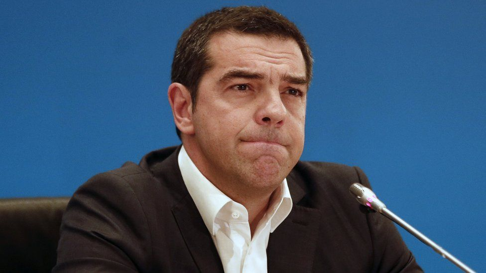 Alexis Tsipras speaks to reporters with a furrowed brow, pursing his lips