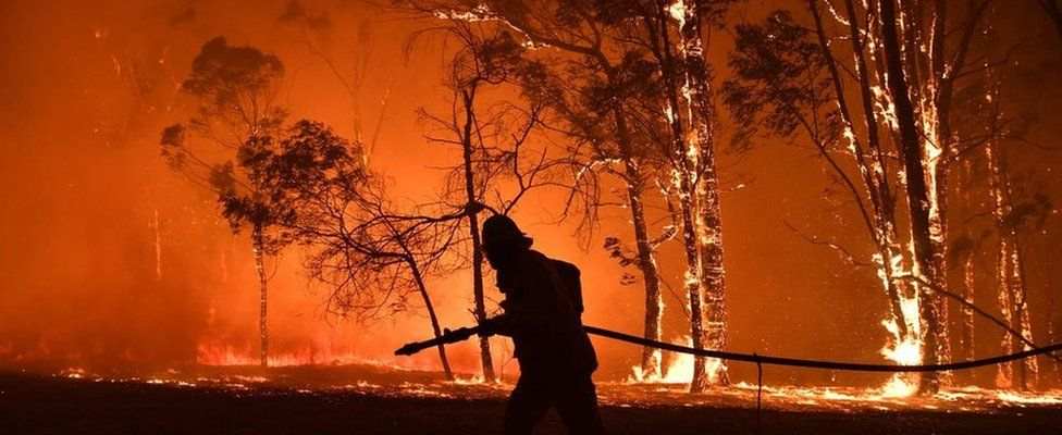Firefighter in front of bushfire