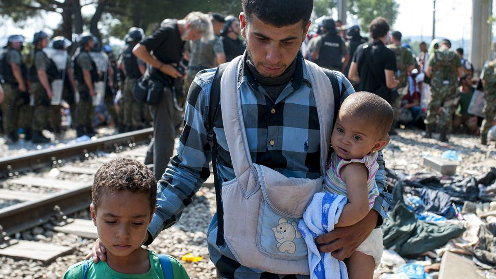 A man walks with children as police officers stand at the border line between Greece and Macedonia near the town of Gevgelija on August 26, 2015.