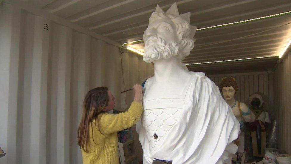 Painter Sarah Brown working on a figurehead