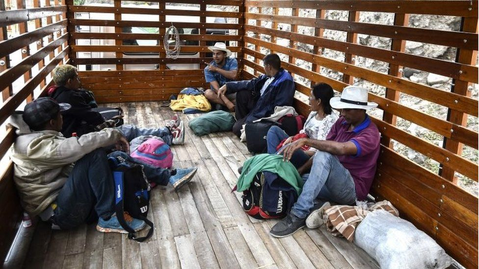Venezuelan migrants travel in the back of a truck on the Pan-American highway, between Pasto and Ipiales, Colombia on their way to Peru, on August 23, 2018.