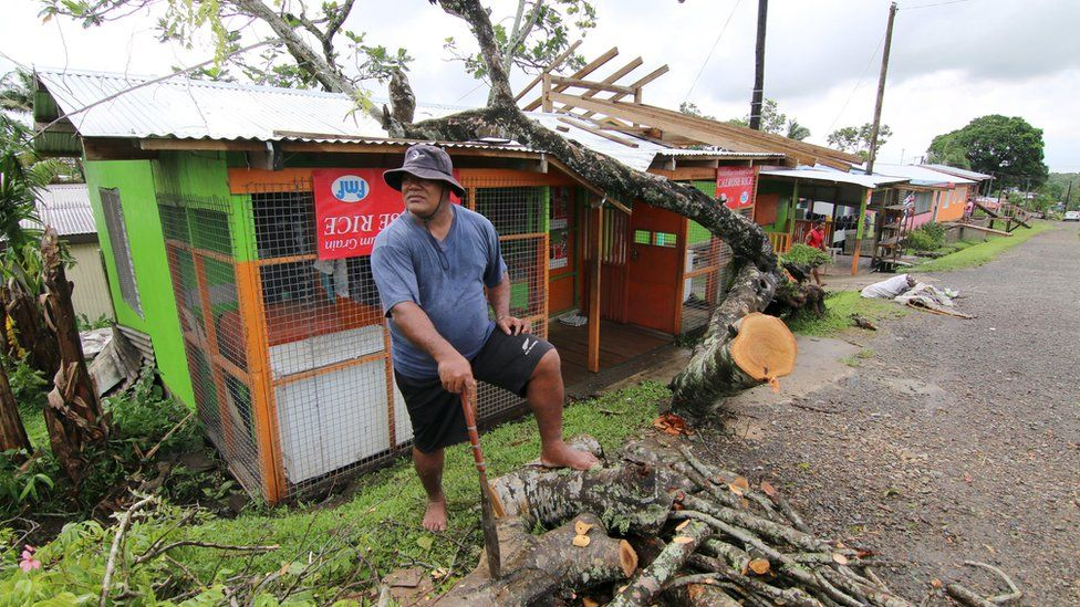 A man chops up a tree that hit his shop