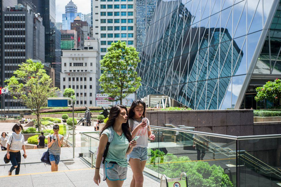 Two girls use their phones in the Central district of Hong Kong on July 26, 2016.