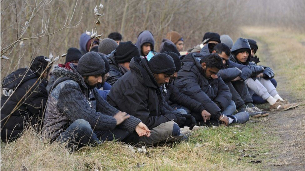 Detained migrants who arrived via Serbia sit near the border village of Roszke, Hungary, 9 February 2016