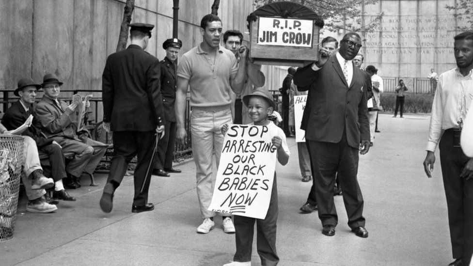 """Demonstrators carry a mock coffin labeled """"RIP Jim Crow,"""" while a little boy parades with a sign saying """"Stop arresting our black babies now,"""" in front of the United Nations."""