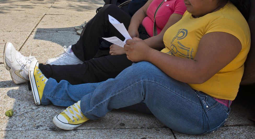 A woman with obesity sits on the pavement in Mexico City on May 20, 2013
