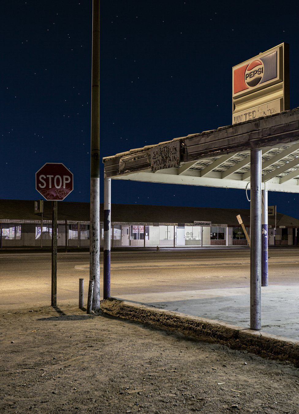 A night view of an abandoned fuel station in an empty street under a starlit sky