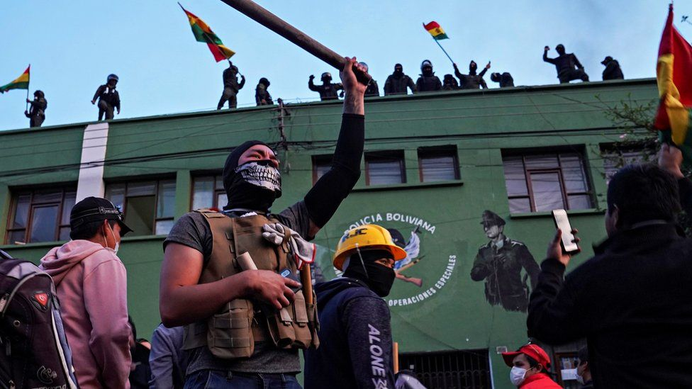 Opponents of Bolivia's President Evo Morales react as police officers stand on the roof of their headquarters, in Cochabamba, Bolivia