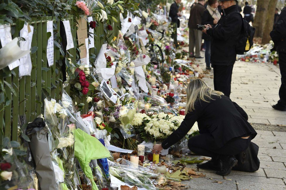 A woman lights a candle in front of a makeshift memorial near Bataclan