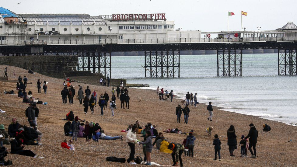People sit on Brighton beach, East Sussex. Picture date: Friday April 2, 2021.