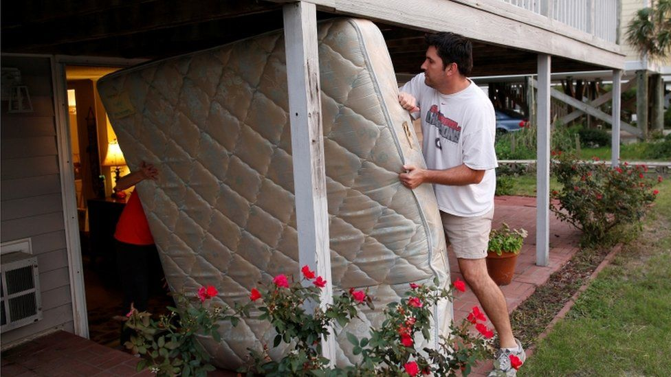 A man and a woman moving a mattress from a house in South Carolina on 4 October 2016