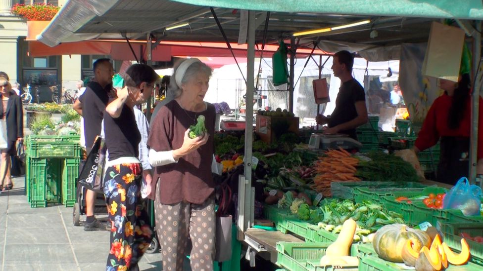 A number of people examine fresh produce at a farmer's market