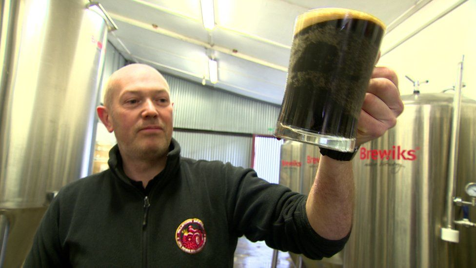 Nigel Logan with the stout he gives to his cattle and sells to customers