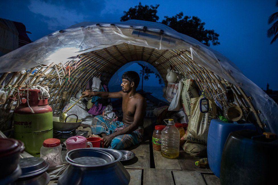 Fisherman Lokman Miah cooking on a fishing boat in Bhola, Bangladesh in 2017