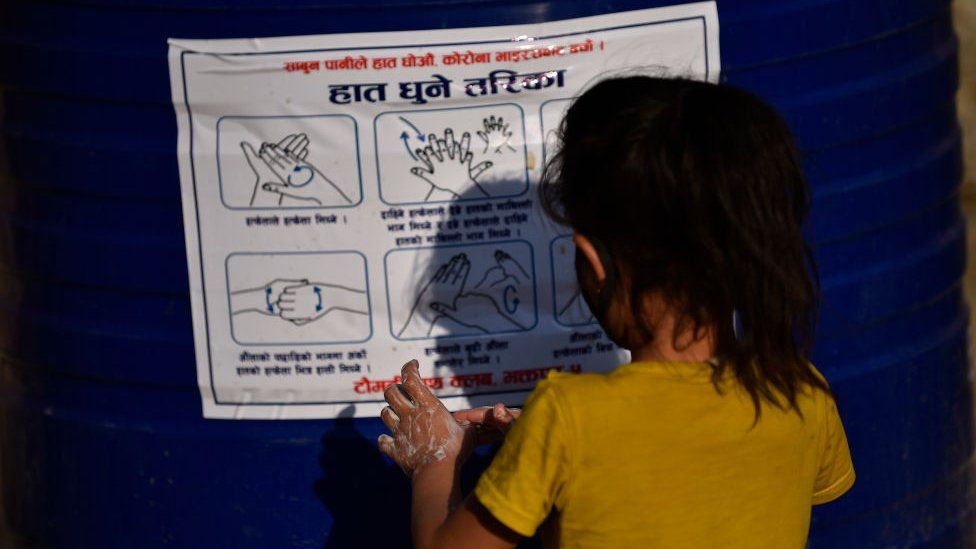 Непальская девочка перед плакатом о правильном мытье рук