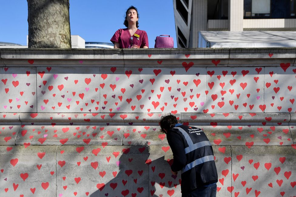 A health worker stands behind a wall painted in hearts, on 29 March 2021