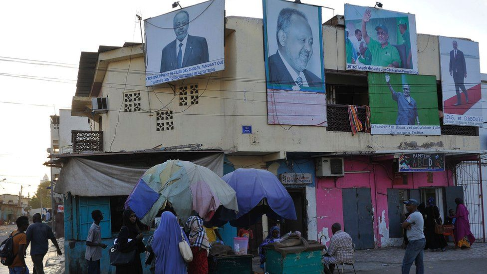 People walk past a house with billboards displaying portraits of incumbent Djibouti President Ismail Omar Guelleh in Djibouti
