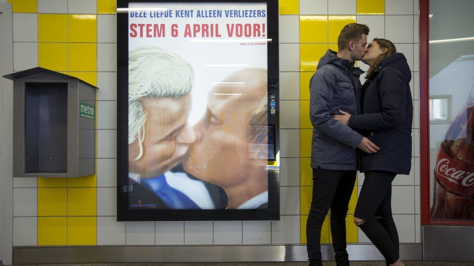 A couple stands next to a poster depicting Dutch politician Geert Wilders and Russian President Vladimir Putin kissing (3 April)