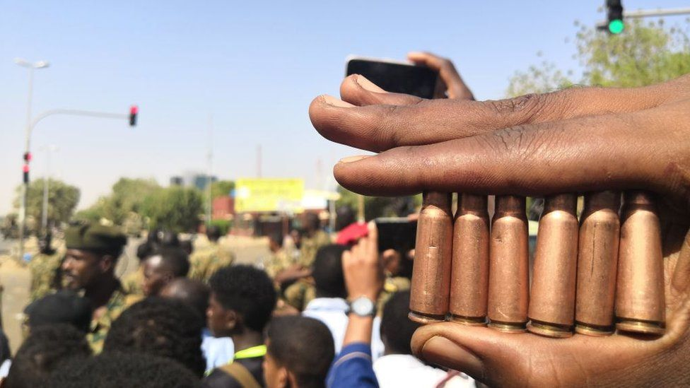 A Sudanese protester shows bullet cartridges as others gather in front of security forces during a demonstration in the area of the military headquarters in the capital Khartoum on 8 April 2019