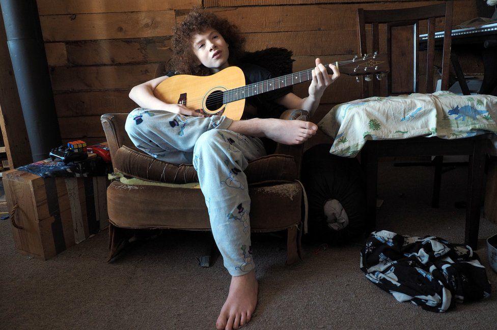 Sky plays guitar