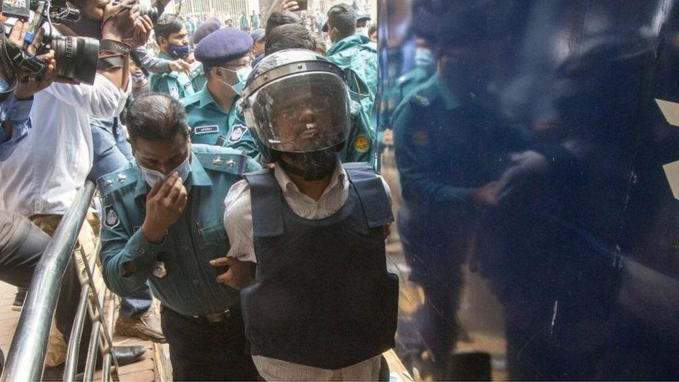 Wearing a helmet and a ballistic vest, one of the accused murderers (R) of blogger-writer Avijit Roy is escorted to the court in Dhaka, Bangladesh, 16 February 2021.