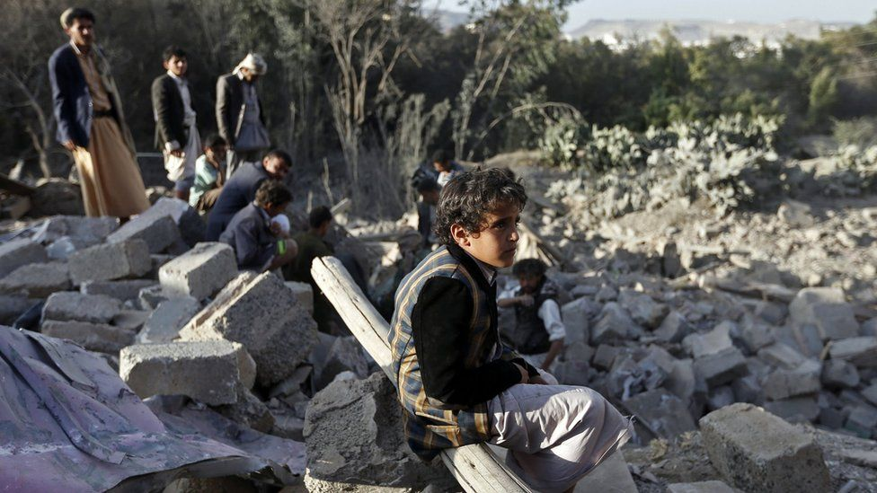 A Yemeni boy sits amid the rubble of damaged houses following a reported Saudi-led coalition air strike on the outskirts of the capital Sanaa on 1 February 2017