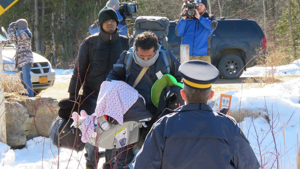 A group of asylum seekers cross the border illegally from the United States into Canada
