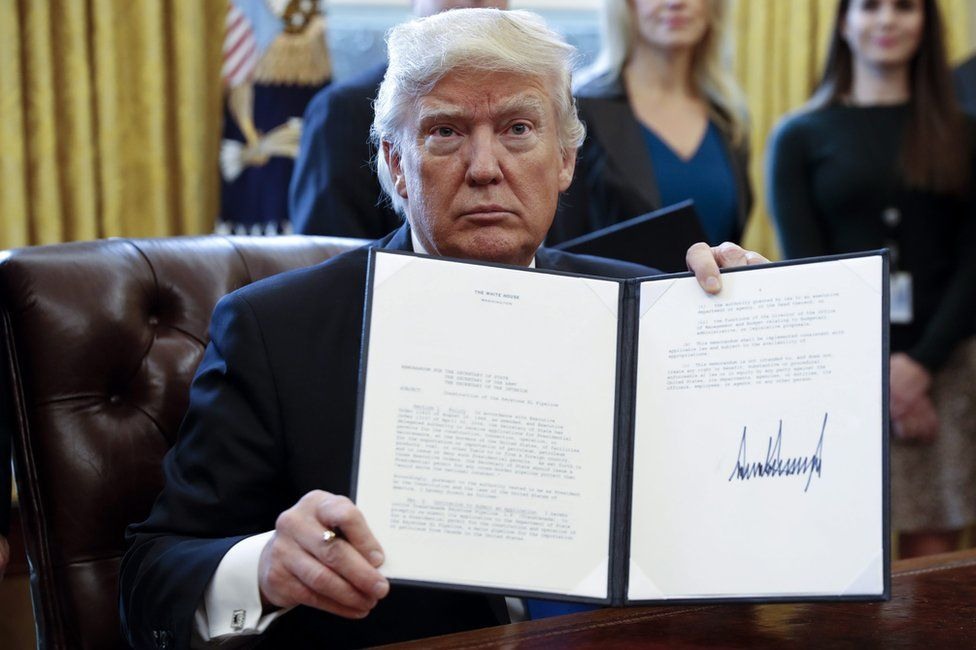 US President Donald Trump displays one of five executive orders he signed related to the oil pipeline industry in the oval office of the White House in Washington, DC, USA, 24 January 2017