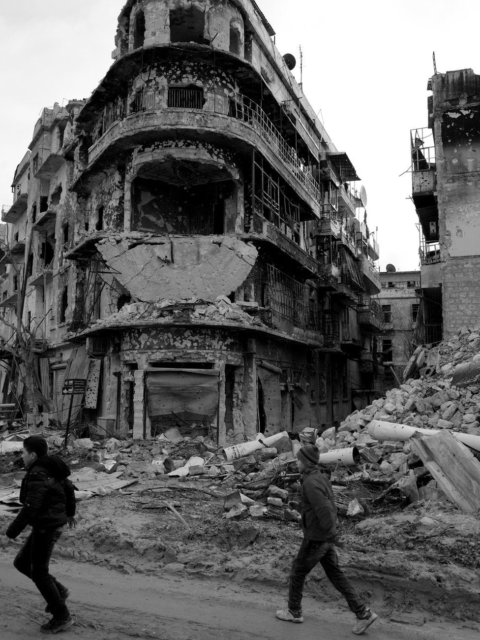 Children walk past war-damaged buildings in Aleppo