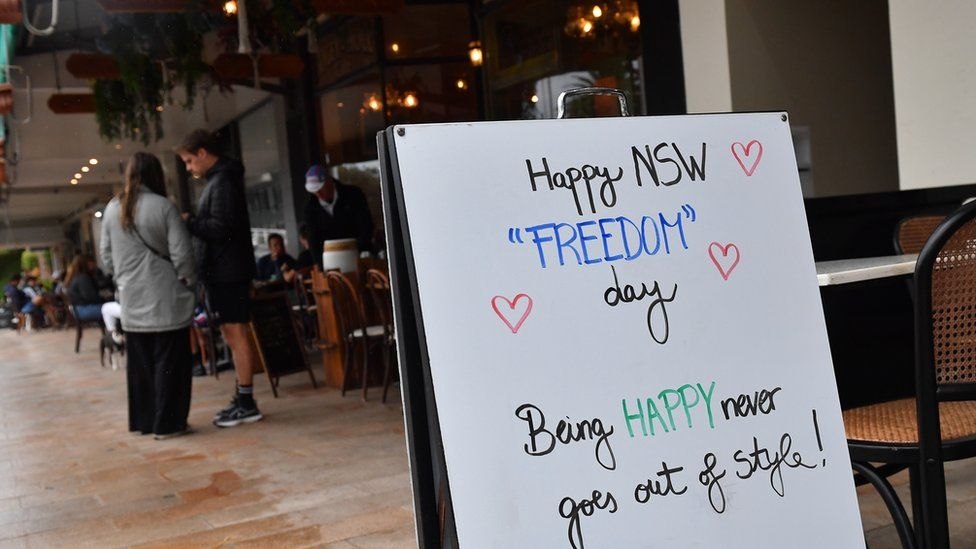 """A sign outside a cafe reads: """"Happy NSW 'Freedom' Day. Being happy never goes out of style"""""""