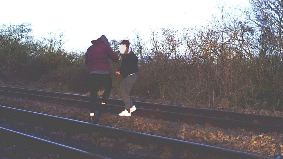 Teenage girls on railway tracks