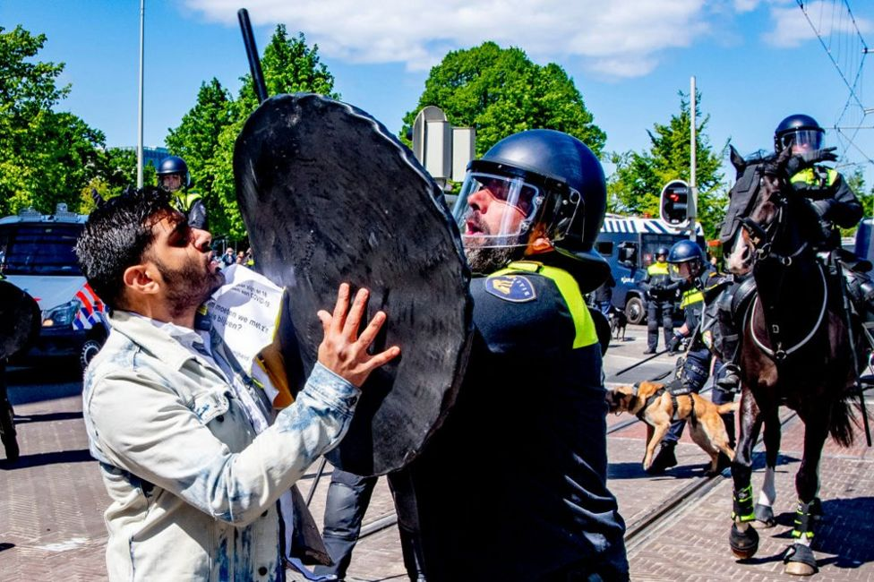 A demonstrator clashes with a riot police officer