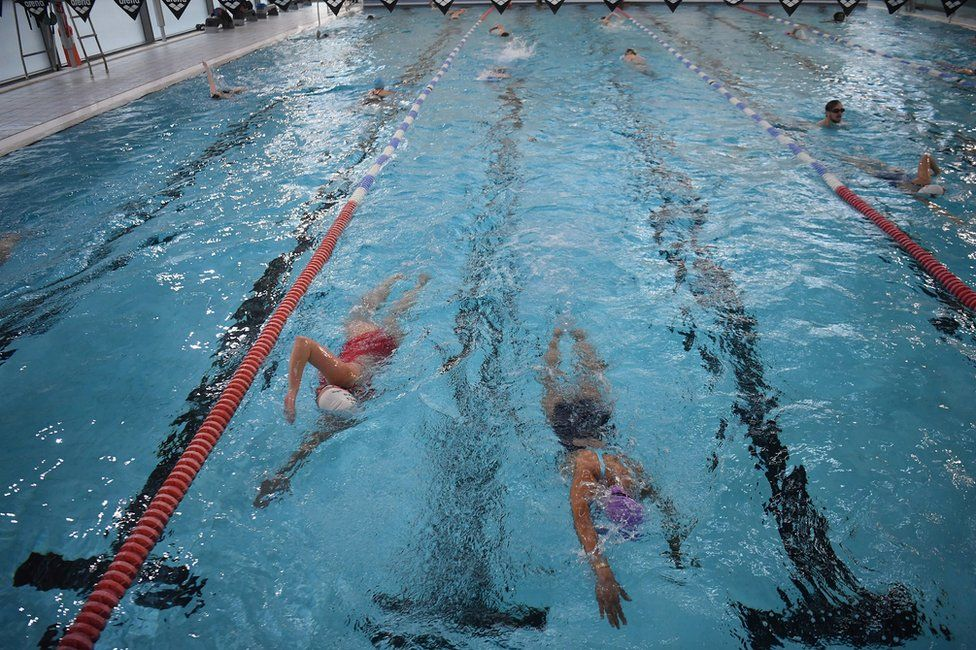 People swim in lanes at an indoor swimming pool