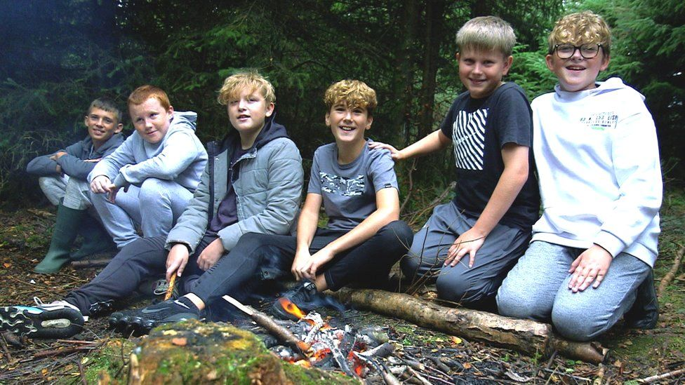 12 and 13-year-old boys sitting around campfire