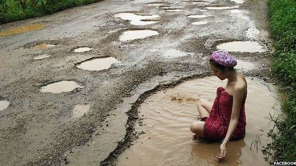Woman bathing in pothole in Thailand